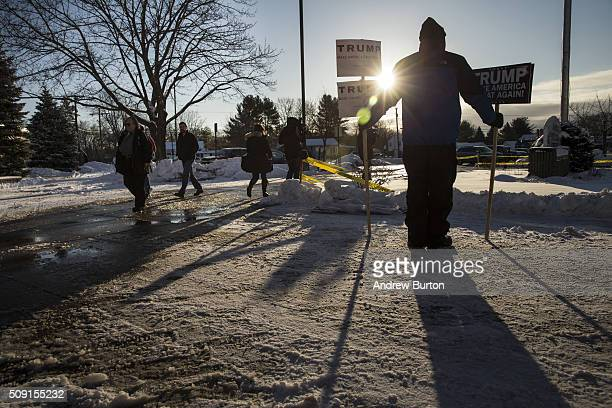 A man holds signs supporting Donald Trump as voters arrive to cast their ballot in the New Hampshire state primary at Manchester High School on...