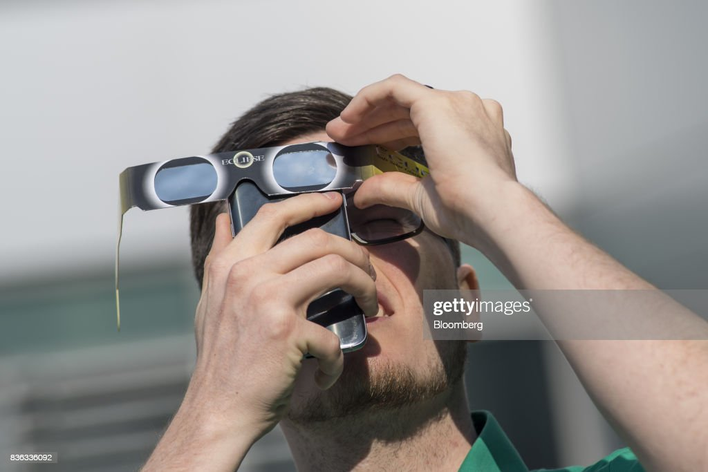 A man holds solar viewing glasses over the camera of a mobile device to take a photograph of the solar eclipse at the California Independent System Operator (ISO) headquarters in Folsom, California, U.S., on Monday, Aug. 21, 2017. Millions of Americans across a 70-mile-wide (113-kilometer) corridor from Oregon to South Carolina will see the sky darken as the sun disappears from view total during the eclipse. Photographer: David Paul Morris/Bloomberg via Getty Images
