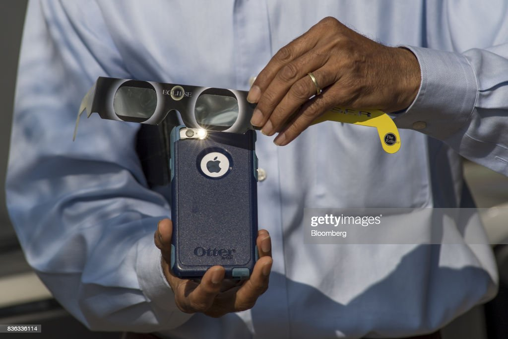 A man holds solar viewing glasses over the camera of an Apple Inc. iPhone to take a photograph of the solar eclipse at the California Independent System Operator (ISO) headquarters in Folsom, California, U.S., on Monday, Aug. 21, 2017. Millions of Americans across a 70-mile-wide (113-kilometer) corridor from Oregon to South Carolina will see the sky darken as the sun disappears from view total during the eclipse. Photographer: David Paul Morris/Bloomberg via Getty Images