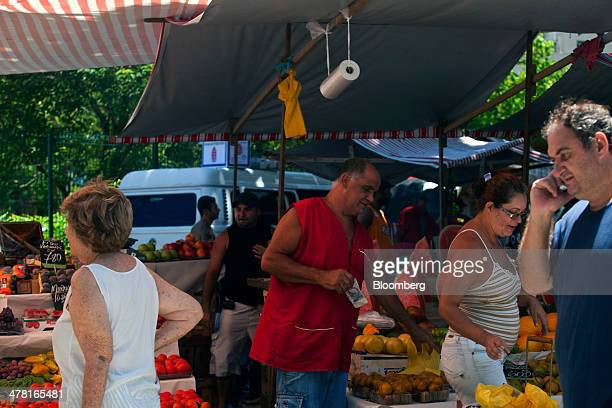 A man holds some cash in his hand at a market in the Ipanema neighborhood of Rio de Janeiro Brazil on Tuesday March 11 2014 Brazils consumer prices...