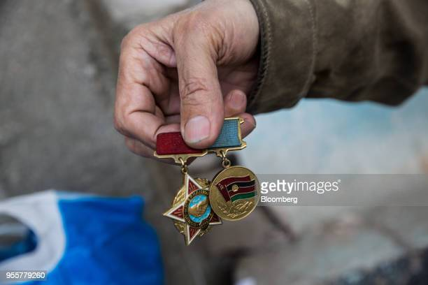 A man holds Soviet era medals for a photograph at a roadside market in Dushanbe Tajikistan on Sunday April 22 2018 Flung into independence after the...