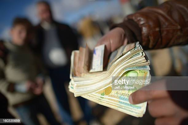 A man holds Syrian money as refugees go about their daily business in the Za'atari refugee camp on January 29 2013 in Mafraq Jordan Record numbers of...