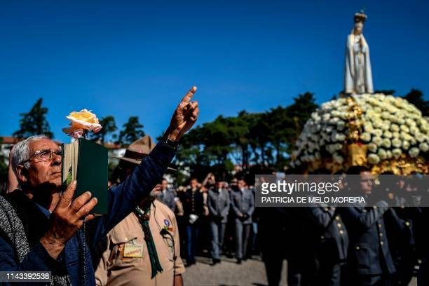 Man holds the Bible and a rose as the statue of Our Lady Fatima passes during a procession at the Fatima shrine in Fatima, central Portugal, on May...