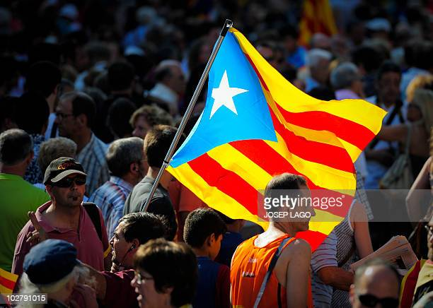 A man holds the Catalan flag as hundreds of thousands of people march on July 10 2010 in Barcelona in support of the Catalan region's statute of...