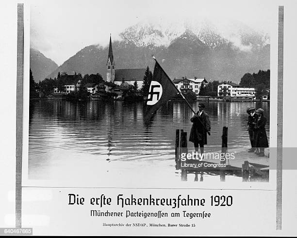 A man holds the first Nazi flag next to the Tegernsee Lake in Munich 1920