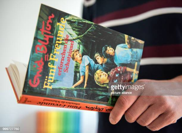 ILLUSTRATION A man holds the first novel of the adventure series 'Famous Five' written by Enid Blyton in his hands in Gelsenkirchen Germany 04...