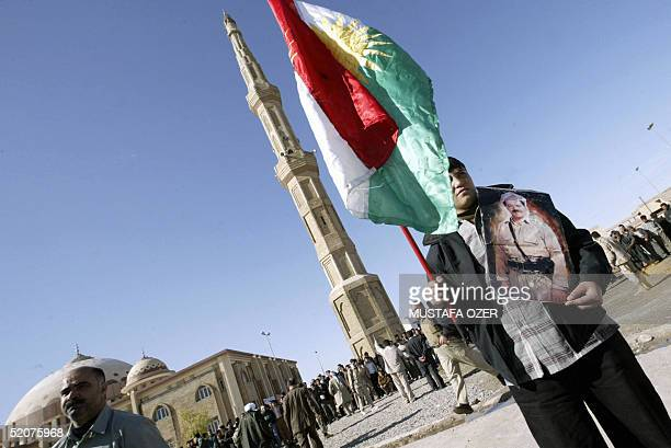 A man holds the Kurdish flag and a poster of Kurd leader Masud Barzani outside the Savaf mosque during the Friday pray in the northern Iraqi Kurdish...