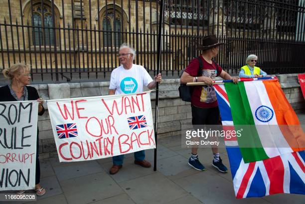 A man holds the national flag of India over the Union Jack next to Pro leave supporters on the day after Parliament voted to take control of...
