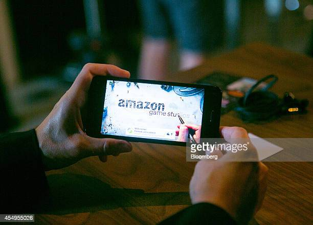 A man holds the new Fire smartphone by Amazoncom Inc and uses the company's game studio to demonstrate the phone's applications during a news...
