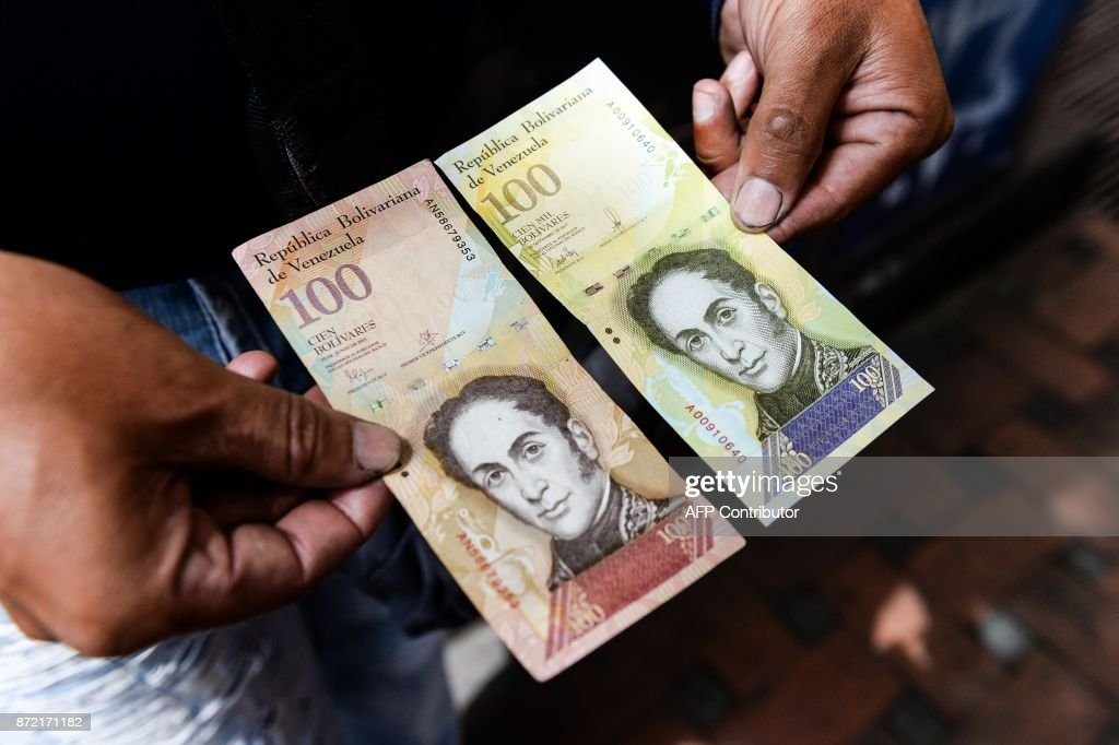 A man holds the new one hundred thousand-Bolivar-note (R) comparing it to the one hundred note, to show the resemblance between both bills in Caracas on November 9, 2017. The new bill is worth 29,89 US dollars in the official market and 2 dollars in the black market at November 9, 2017 exchange rate. /