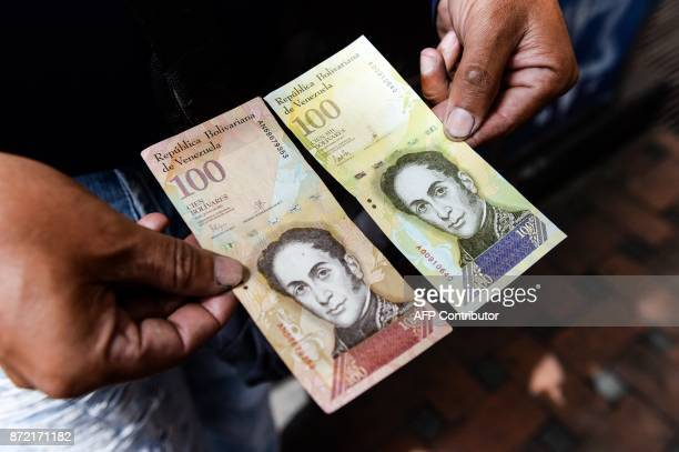 A man holds the new one hundred thousandBolivarnote comparing it to the one hundred note to show the resemblance between both bills in Caracas on...