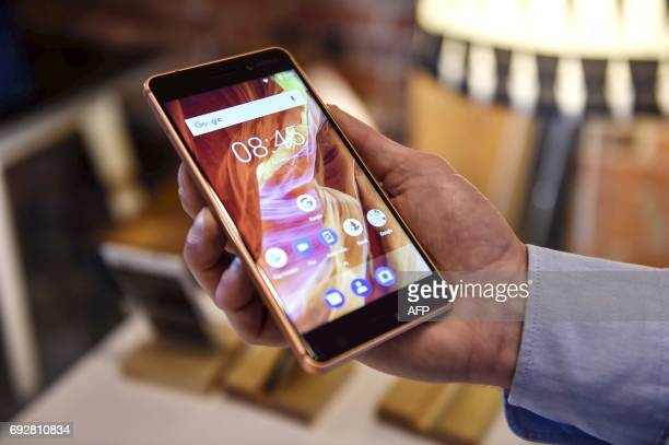 Man holds the Nokia smartphone model 6 during a press conference of Finnish mobile phone maker HMD Global in Helsinki, on June 6, 2017. / AFP PHOTO /...
