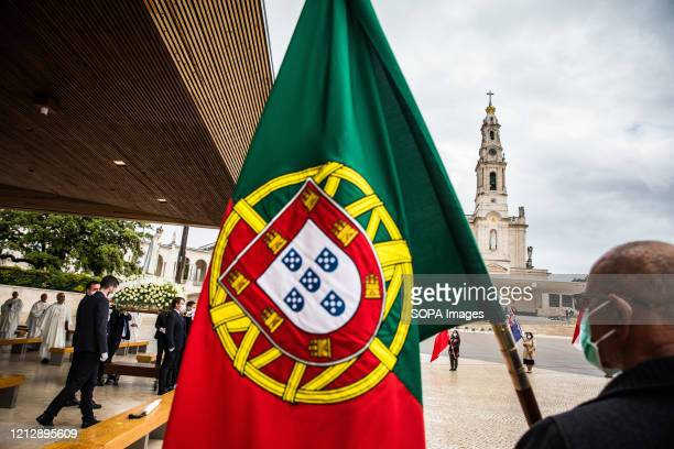 A man holds the Portuguese flag next to the figure of Our Lady of Fatima during the apparition Due to the COVID19 pandemic this year's ceremonies are...