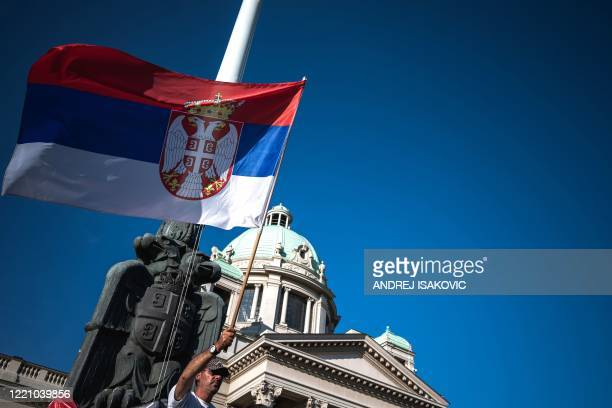 Man holds the Serbian national flag during a protest in front of the National assembly building in Belgrade on June 18, 2020. - Serbians are to vote...