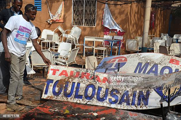A man holds the sign of 'Le Toulousain' a French bar in Niamey after it was burned by demonstrators protesting against French satirical weekly...