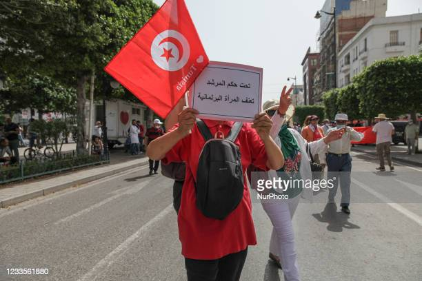 Man holds the Tunisian flag as he raises a placard that reads in Arabic under the governance of the Muslim Brotherhood's Supreme Guide, the woman...