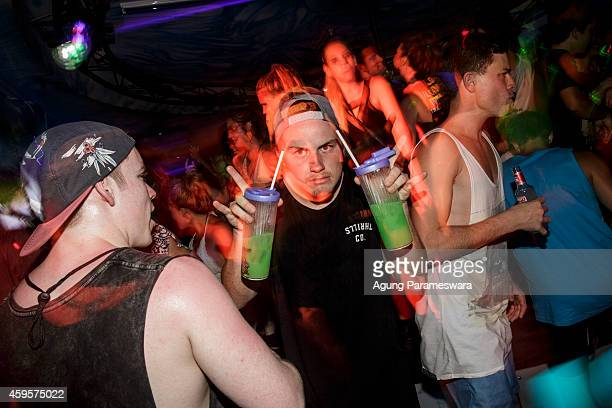 A man holds two bottles of cocktails at a party in a night club during Australian 'schoolies' celebrations on November 26 2014 in Kuta Bali Indonesia...