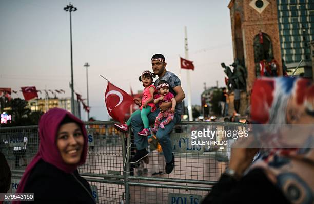 TOPSHOT A man holds two children and a Turkish flag in Istanbul's Taksim Square on July 24 2016 during the first crossparty rally to condemn the coup...