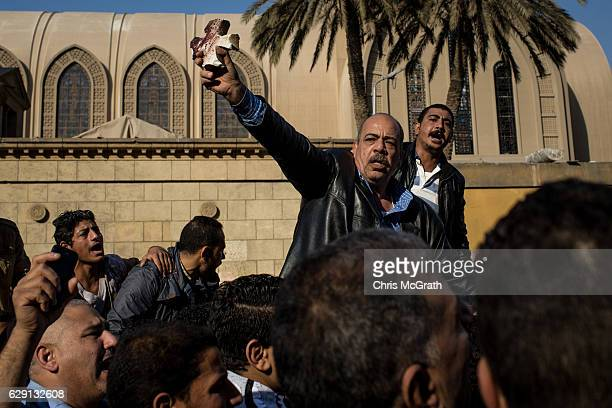 A man holds up a bloodied piece of rubble in the shape of a cross as people rallied in the street outside the church of St Peter and St Paul in the...