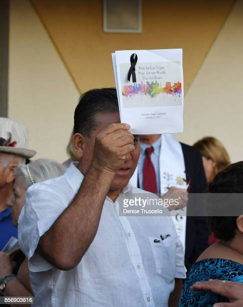 Man holds up a booklet during a vigil at Guardian Angel Cathedral for the victims of the Route 91 Harvest country music festival shootings on October...