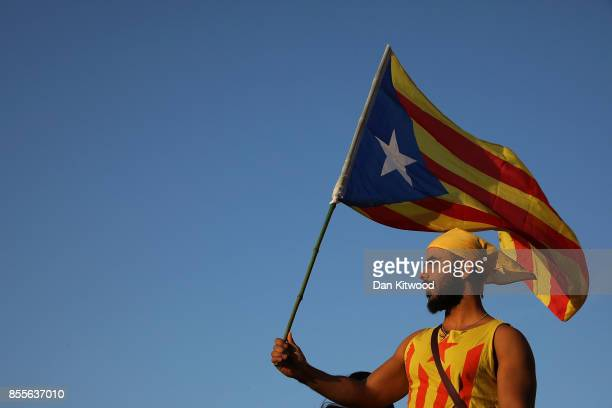 A man holds up a Catalan flag as people gather at the final proindependence rally at Plaza Espana ahead of Sunday's referendum vote on September 29...