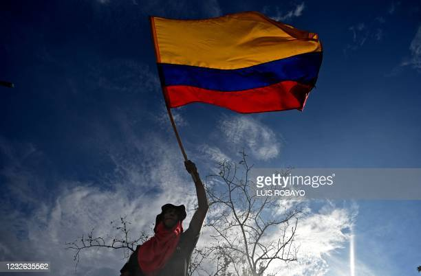 Man holds up a Colombian flag during a protest against a tax reform bill they say will leave them poorer as the country battles its deadliest phase...