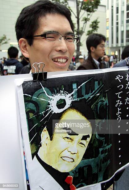 A man holds up a comic book image of Taro Aso Japan's prime minister at Aso's campaign rally in the Akihabara district of Tokyo Japan on Sunday Oct...