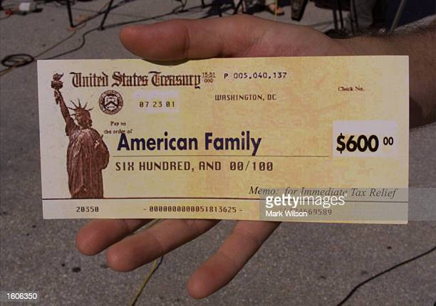 A man holds up a copy of a tax refund check August 2 2001 outside the US Capitol in Washington DC