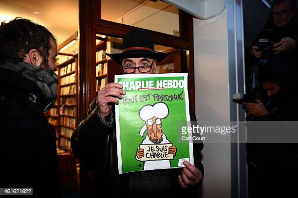 Man holds up a copy of Charlie Hebdo magazine as he leaves a French bookstore on January 16, 2015 in London, England. People queued since the early...