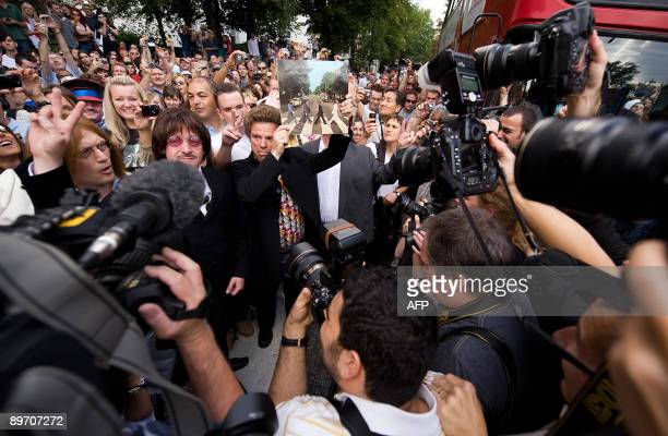 A man holds up a copy of the Beatles album as he crosses Abbey Road on August 8 2009 during an event to celebrate 40 years to the minute since the...