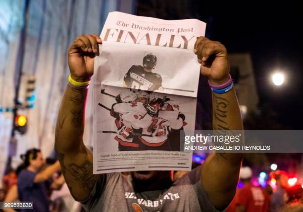 Man holds up a copy of The Washington Post as Washington Capitals fan celebrate after the Washington Capitals won Game 5 of the Stanley Cup Final...