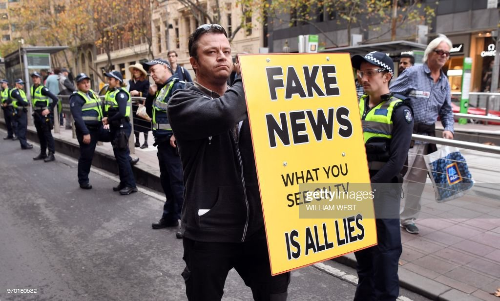 A man holds up a 'Fake News' placard as members of the Australian Liberty Alliance (ALA) and supporters protest outside the British consulate in support of jailed British right-wing activist and former leader to the English Defence League (EDL) Tommy Robinson, aka Stephen Christopher Yaxley-Lennon, in Melbourne on June 9, 2018. - The ALA are conducting protests outside British consulates around the country in support of Robinson