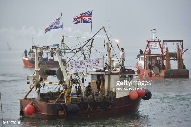 A man holds up a flare on a boat during a demonstration in Whitstable southeast England on April 8 2018 against the Brexit transition deal that would...