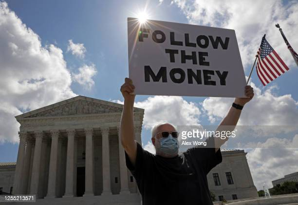 """Man holds up a """"Follow the Money"""" sign in front of the U.S. Supreme Court July 9, 2020 in Washington, DC. The Supreme Court has issued a 7-2 ruling..."""