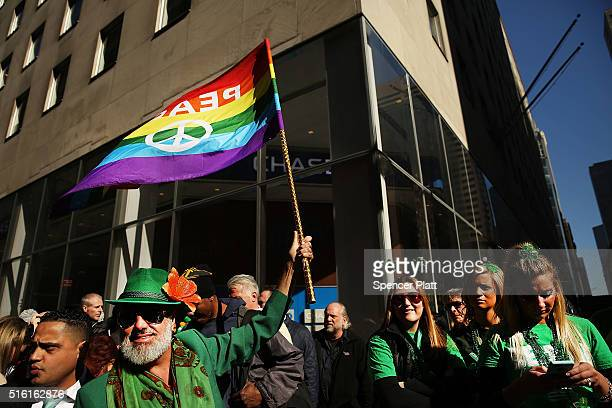 A man holds up a Gay Pride flag at the annual St Patrick's Day parade one of the largest and oldest in the world on March 17 2016 in New York City...