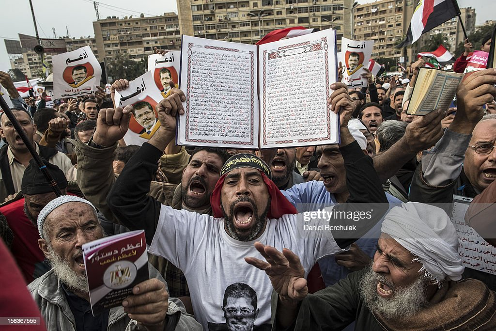 A man holds up a koran as supporters of Egyptian President Mohamed Morsi and members of the Muslim Brotherhood chant slogans during a rally on December 14, 2012 in Cairo, Egypt. Opponents and supporters of Egyptian President Mohamed Morsi staged final rallies in Cairo ahead of tomorrow's referendum vote on the country's draft constitution that was rushed through parliament in an overnight session on November 29. The country's new draft constitution, passed by a constitutional assembly dominated by Islamists, will go to a referendum vote on December 15.