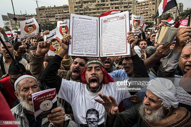 A man holds up a koran as supporters of Egyptian President Mohamed Morsi and members of the Muslim Brotherhood chant slogans during a rally on...