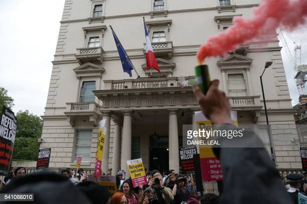 A man holds up a lit flare among prorefugee activists rallying outside the French Embassy in central London on June 18 2016 during a protest after...