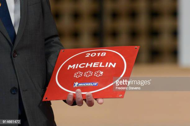 A man holds up a Michelin three star plaque at Philharmonie De Paris on February 5 2018 in Paris France The 2018 Michelin Guide the little red book...