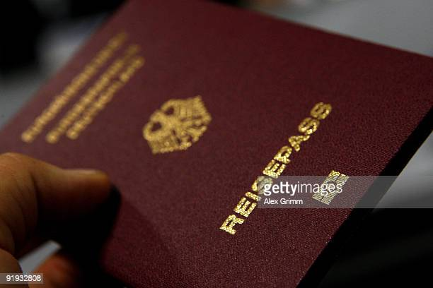 A man holds up a passport with the EasyPass sign at the bottom during the presentation of the new automated border control system easyPass at...