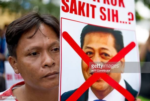 A man holds up a photograph of house speaker Setya Novanto with redcross on it during a rally in front of the South Jakarta court on September 12 as...