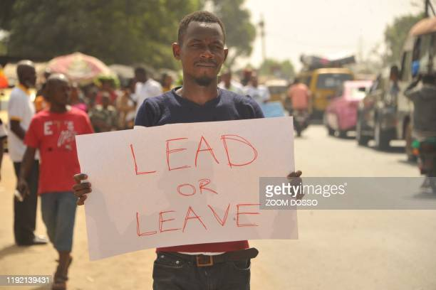 Man holds up a placard as members of the Council of Patriots protest against the deepening economic crisis under Liberian President George Weah, in...