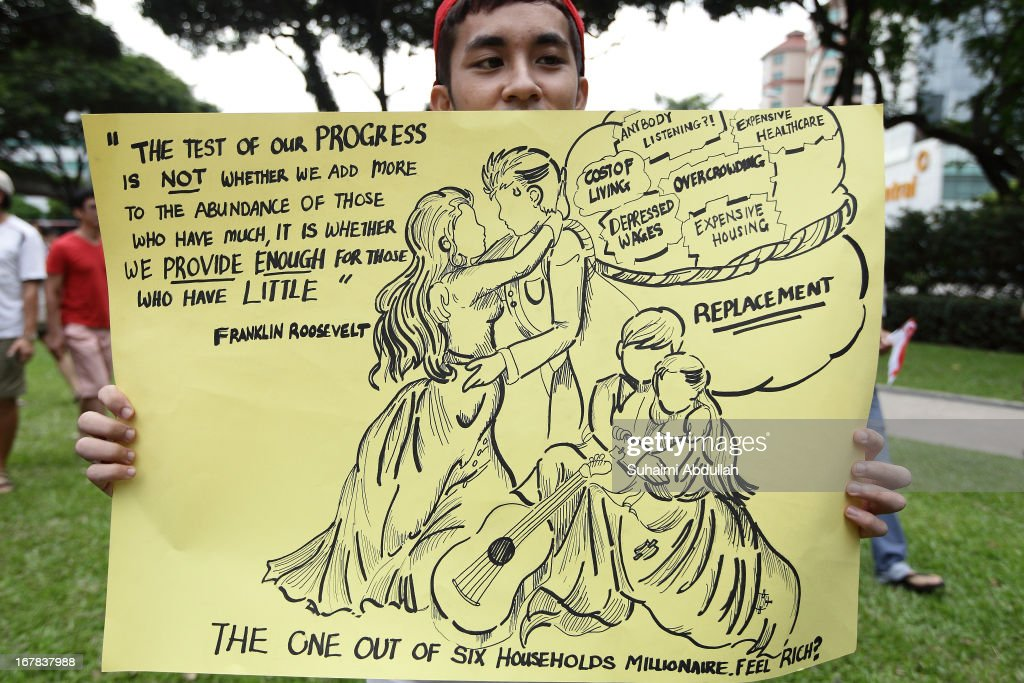 A man holds up a placard during a protest against the government's White Paper on Population and labour-related matters that affect Singaporeans at Speakers' Corner in Hong Lim Park on May 1, 2013 in Singapore. Thousands of protesters gathered today in an inaugural labour day protest against the 6.9 million population government white paper that revealed it could increase 30% to 6.9 million by 2030, angering residents who already see a strain on housing, transportation and healthcare. This is a follow up protest after one was held on 16 Feb, 2013 organised by the same organiser, transitioning.org