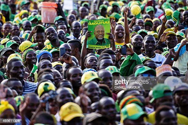 A man holds up a poster of presidential candidate John Magufuli during a ruling Chama Cha Mapinduzi rally in Dar es Salaam Tanzania on October 21...