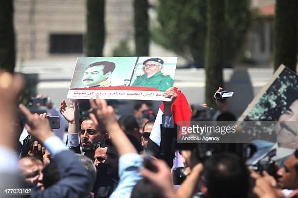 A man holds up a poster of Saddam Hussein and Tariq Aziz during the funeral of Tariq Aziz in Amman Jordan on June 13 2015 Tariq Aziz former deputy...