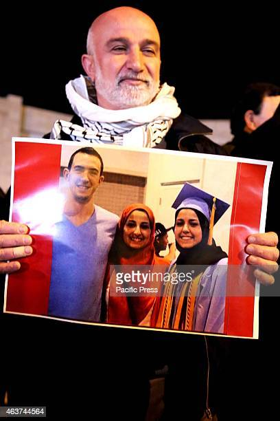 A man holds up a poster of the three slain Muslim students from Chapel Hill during a vigil in the West Bank city of Beit Sahur Following another...