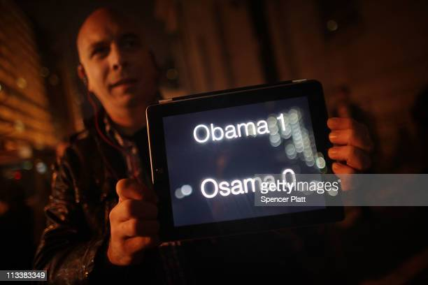 A man holds up a scoreboard on his ipad displaying Obama one Osama nil as thousands of people celebrate in the streets at Ground Zero the site of the...