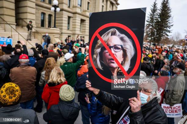 Man holds up a sign against Rep. Liz Cheney as Rep. Matt Gaetz speaks to a crowd during a rally against her on January 28, 2021 in Cheyenne, Wyoming....