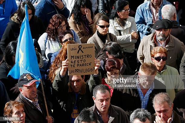 Man holds up a sign as miners, family members and locals gather on October 29, 2013 in Pola de Gordon northwestern Spain in memory of six miners who...