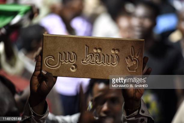 Man holds up a sign as Sudanese protesters wave flags and flash victory signs as they gather for a sit-in outside the military headquarters in...